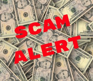 Scam Alert in red letters over dollars